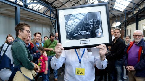 John Conroy, historian  with a framed photo of the markets  (1940's)talking to visitors  to the Wholesale Fruit Market on Mary's Lane in Dublin  as part of the architecture weekend open day. Photo: Cyril Byrne / THE IRISH TIMES