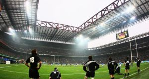 Luke McAlister of New Zealand kicks a penalty as the New Zealand substitutes look on from behind the posts during the sold out   match between Italy and New Zealand at the San Siro in November 2009. Photograph:  Paul Gilham/Getty Images