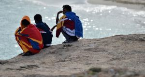 Surviving African immigrants from Thursday's boat-wreck tragedy off Lampedusa island look on at Guitgia Beach yesterday in Lampedusa, Italy. Photograph: Tullio M. Puglia/Getty Images