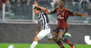 Juventus' Carlos Tevez  is challenged by AC Milan's Kevin Constant during their  Serie A match  in Turin. Photograph:  Giorgio Perottino/Reuters