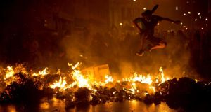 A demonstrator with his face covered jumps over a burning barricade at Cinelandia square during a march in support of teachers on strike in Rio de Janeiro, Brazil. Teachers have been on strike demanding better pay for almost two months. Photograph: Felipe Dana/AP