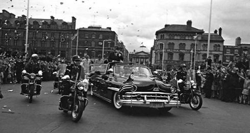 Grattan Bridge - JFK Visit (1963) John F. Kennedy waves to onlookers as the presidential motorcade crosses Grattan Bridge during his visit in June 1963.  © Irish Photographic Archive