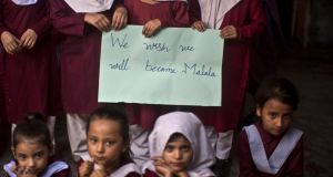 Pakistani schoolchildren hold a handwritten sign during a special class to commemorate the anniversary of Malala Yousufzai's shooting at a school in Rawalpindi, Pakistan, today. Photograph: AP