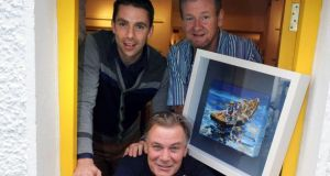 Chef Derry Clare with Kerry footballer Marc O'Se and artist Liam O'Neill pictured at the Dingle Food Festival where they raised about €5,000 for the KerryCork Health Link Bus by holding raffle of a painting of Blasket Islanders and a mutton pie tasting. Photograph: Don MacMonagle