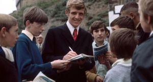 Eamon Dunphy signing autographs for young fans outside his club Millwall's ground in 1970. 	Photograph: Hulton Archive
