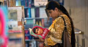 "A woman browses a copy of Malala Yousufzai's book ""I am Malala"" at a book store in Islamabad. Photograph: Reuters"