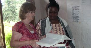 Tanzania: retired student adviser Ros McFeely donating books from Ireland to a librarian at Lupanga Secondary School