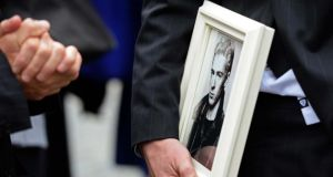 A mourner carries a framed photograph at Phil Chevron's funeral at the Mansion House in Dublin today. Photograph: Eric Luke/The Irish Times