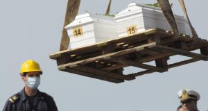 The caskets of two children who died when their boat capsized are lifted to be embarked on an Italian navy ship at Lampedusa island harbour at the weekend.  Photograph: Amedeo Fragapane/AP Photo