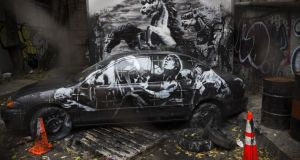 Work from street artist Banksy is seen through a chain link fence last week in the Lower East Side neighbourhood of New York City.Photograph: Andrew Burton/Getty Images