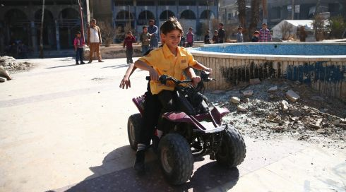 Boys ride on a motorised vehicle as others wait their turn on the first day of Eid al-Adha in the Duma neighbourhood in Damascus, Syria. Photograph: Bassam Khabieh/Reuters