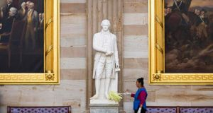 A cleaner dusts a statue of Alexander Hamilton, a founding father of the US, in the Rotunda on Capitol Hill in Washington yesterday as the US government shutdown entered a third week. Photograph: Joshua Roberts/Reuters