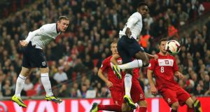 England's Wayne Rooney scores England's first-half goal as Danny Welbeck follows the ball during their World Cup qualifying match against Poland at Wembley. Photograph: PA