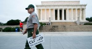 "Richard Trott, a National Park Service park ranger, removes ""Closed"" signs near the Lincoln Memorial after the government reopened in Washington DC. Photograph: Doug Mills/The New York Times"