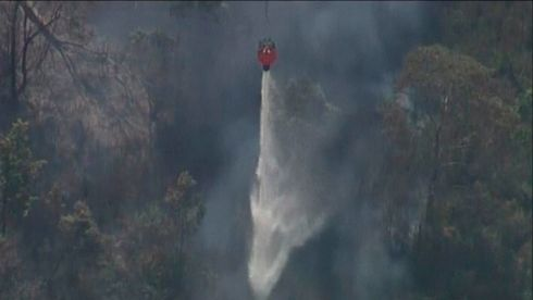 A helicopter releases water over bushfires in Lithgow, New South Wales, in this still frame taken from an October 17th, 2013 video provided by Seven Network Australia.  Photograph: Reuters