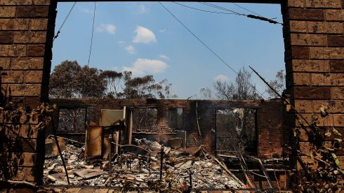 A home completely destroyed by bush fire in Winmalee, Australia. One man was known to have died and dozens of properties were destroyed in bushfires devastating the Blue Mountains and Central Coast regions of New South Wales. Photograph: Lisa Maree Williams/Getty Images