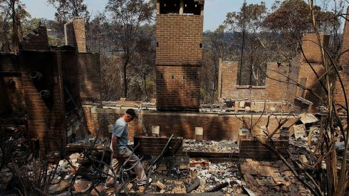Noel Willis inspects his home destroyed by fire in Winmalee, Australia. Photograph: Lisa Maree Williams/Getty Images