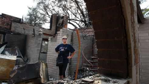 Lyndal Rogers stands in her childhood home destroyed by fire in Winmalee. Photograph: Lisa Maree Williams/Getty Images