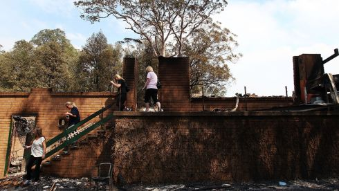 Members of the Rogers family inspect the destruction of their home in Winmalee. Photograph: Lisa Maree Williams/Getty Images