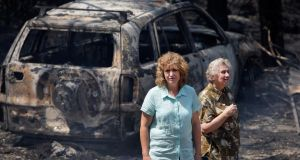 Leanne Brown and her mother Rosemary Booth inspect the remains of her home following severe bush fires  in Winmalee, Australia. Photograph: Lisa Maree Williams/Getty Images