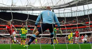 Arsenal's Jack Wilshere (left) scores the first past Norwich City's goalkeeper John Ruddy   at the Emirates Stadium. Photograph: Toby Melville/Reuters