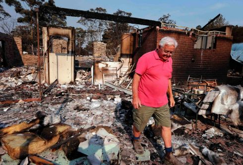 Local resident Alan Seaman walks through the remains of his home, which was destroyed by a bushfire in the Blue Mountains suburb of Winmalee. More than 200 homes have been destroyed since last Thursday as scores of fires burned through thousands of hectares of bush, farms and rural communities outside Sydney. A state of emergency has been declared in New South Wales (NSW) state, Australia's most populous. Photograph: David Gray/Reuters