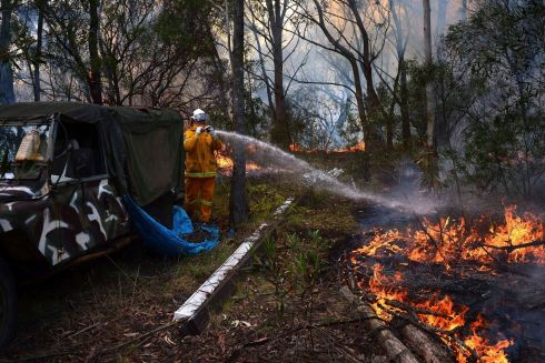 A Rural Fire Service firefighter sprays water onto a small fire burning near a home in western Sydney. Photograph: Reuters/Stringer