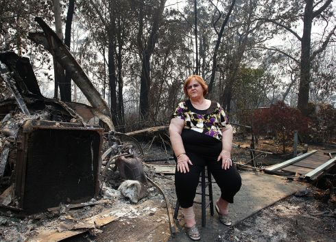 Sue Dunlop sits in the front yard of her home of 41 years in Winmalee which was destroyed by bushfire. Photograph: Lisa Maree Williams/Getty Images