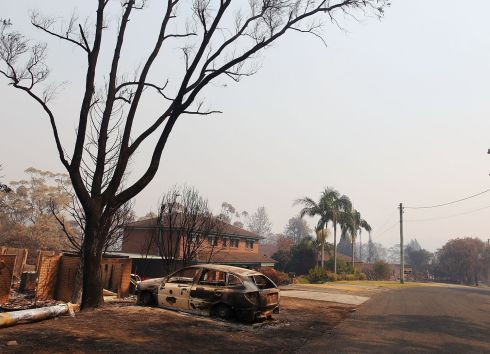 A home and car destroyed by bushfire. Photograph: Lisa Maree Williams/Getty Images