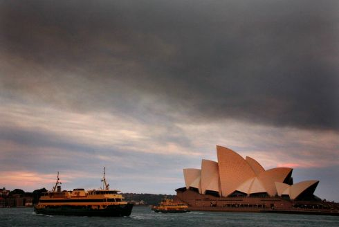 Ferries sail past the Sydney Opera House as smoke from bushfires can be seen above.  Photograph: David Gray/Reuters
