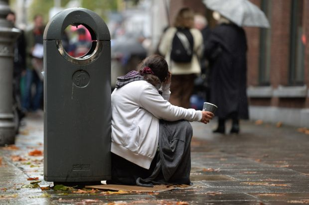 A young woman with a paper cup begging in Dublin city centre. 