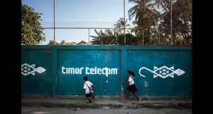 School children on their way to school run past a hand painted Timor Telecom advertisment on a wall. Photograph: Cedric Arnold/realfeatures.com