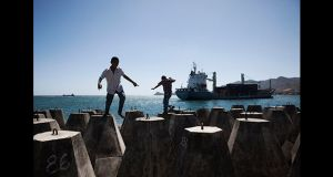 Young boys play on concrete blocks at Dili's port, as a container ship sails in. Photograph: Cedric Arnold/realfeatures.com