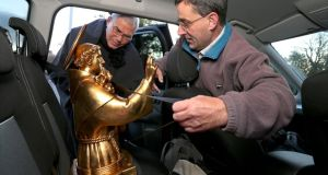 Brothers Joe Fenton and Julio Garcia secure the bust that holds the relics of St Anthony of Padua in the back of the car before leaving Galway Cathedral for Dublin. Photograph: Joe O'Shaughnessy