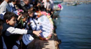 Palestinian schoolchildren throw flowers into the Seaport of Gaza City yesterday to commemorate  Palestinian migrants who died after their boat sank while fleeing Syria to Italy. Photograph: Suhaib Salem/Reuters