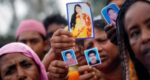 Relatives show pictures of missing garment workers in the wake of the collapse of the Rana Plaza building in Savar, outside Dhaka in April