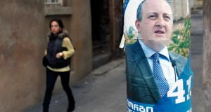 A woman walks past an election poster of presidential candidate Georgy Margvelashvili in Tbilisi. Mr Margvelashvili is expected to win this weekend's election. Photograph: David Mdzinarishvili/Reuters