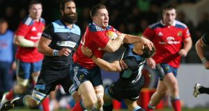 Munster's JJ Hanrahan hands off  Chris Cusiter in Scotstoun. Photograph: Ian McNicol/Inpho