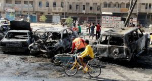 A youth cycles past a man clearing up at the site of a car bomb in Baghdad's al-Shaab district today. Photograph: Thaier Al-Sudani/Reuters