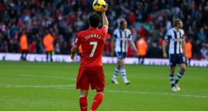 Liverpool's Luis Suarez leaves the pitch at half time after scoring two goals against West Brom.
