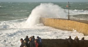 People watch rough seas in the harbour at Porthleven, Cornwall. Photograph: : Ben Birchall/PA Wire