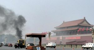 Smoke rises in front of a portrait of Mao Zedong at Tiananmen Square in Beijing after five people were killed and many injured when a car ploughed into pedestrians and caught fire in Beijing's Tiananmen Square.