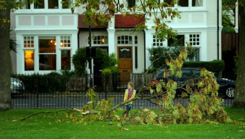 A girl carries a fallen branch in a park in Brixton, London. Photograph: Anthony Devlin/PA Wire
