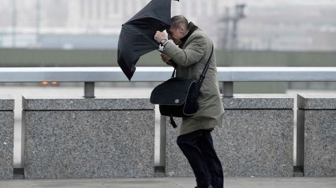 A commuter loses control of his umbrella. Photograph: Dylan Martinez/Reuters