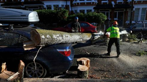 Workers clear a fallen tree from a street in south London. Photograph: Reuters/Andrew Winning