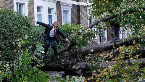 A student, jumps over a fallen tree as he makes his way to school in Islington. Photograph: Olivia Harris/Reuters