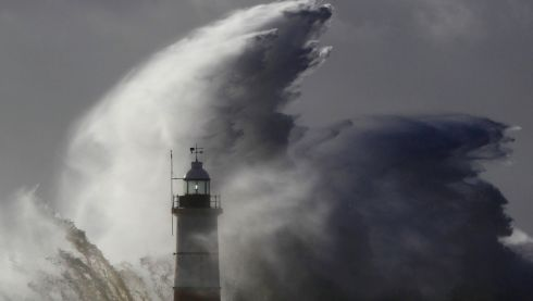 Waves crash against a lighthouse during storms that battered Britain and where a 14-year-old boy was swept away. Photograph: Luke MacGregor/Reuters