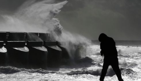 A man watches stormy seas in strong winds as waves crash on the harbour wall at Brighton marina. Photograph: Luke MacGregor/Reuters