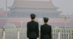 Paramilitary police officers stand guard near Tiananmen Gate on a hazy day in Beijing. Photograph: Jason Lee/Reuters