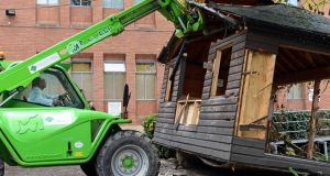 The Master of the Rotunda Hospital Sam Coulter Smith, uses a fork-lift to demolish the existing outdoor smoking cabin, at the rear of the hospital today. Photograph: Eric Luke/The Irish Times.